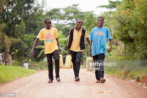 three men with jerrycans - uganda stock pictures, royalty-free photos & images