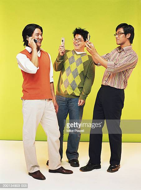 Three men with mobile phones, smiling