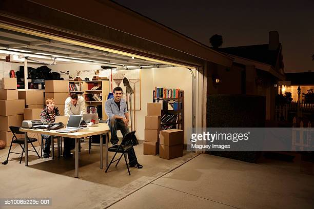three men working at laptops on desk in garage at night - costa mesa stock photos and pictures