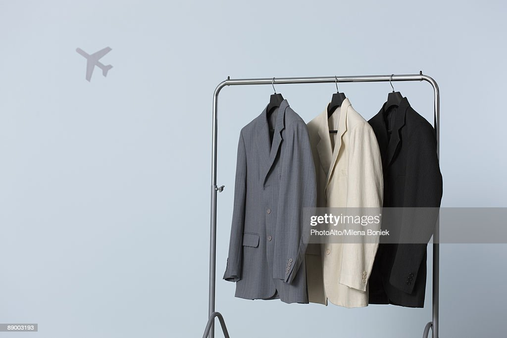 Three men's suit jackets hanging on clothes rack, airplane shape in background : Foto de stock