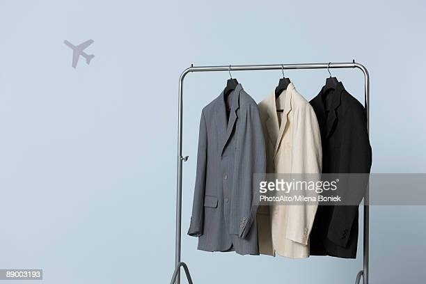 Three men's suit jackets hanging on clothes rack, airplane shape in background