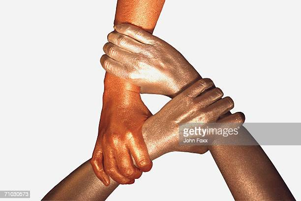 three metallic hands holding each other