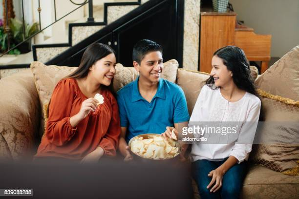 Three mexican siblings sitting on sofa with chips