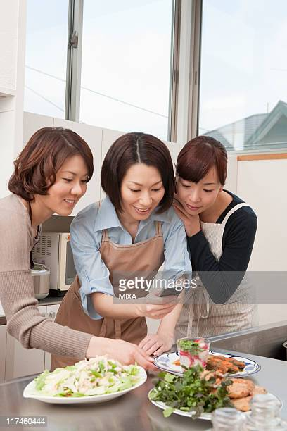 Three mid adult women photographing dishes