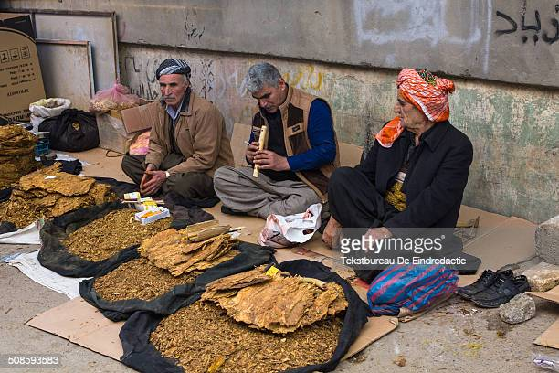 Three middleaged Kurdish street vendors wearing traditional Kurdish clothing baggy trousers and headscarfs selling tobacco smoking and making music...