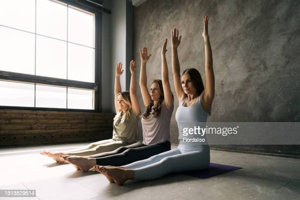 three middle-aged women sitting on sports mats in a meditation hall with their hands up - mid section stock pictures, royalty-free photos & images