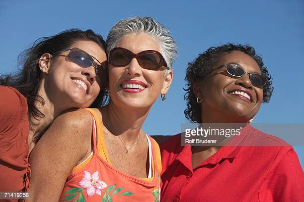 three middle-aged women smiling - only mature women stock pictures, royalty-free photos & images