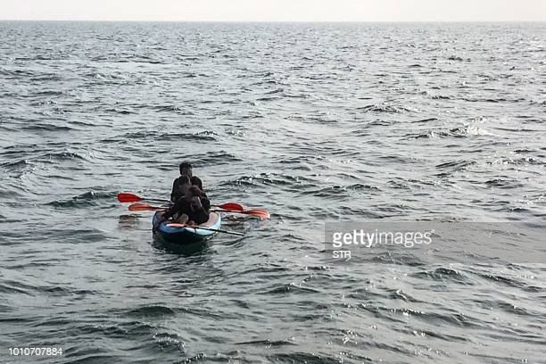 Three migrants who were attempting to cross The English Channel from France to Britain are seen as they drift in an inflatable canoe off the French...