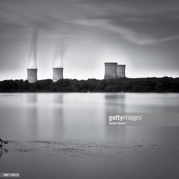 CONTENT] Three Mile Island Nuclear Power Plant cooling towers with steam forming clouds above them as seen from across a still river with towers...