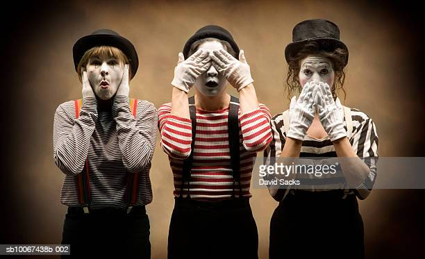 three mimes acting out 'hear no evil, see no evil, speak no evil' - mime stock photos and pictures