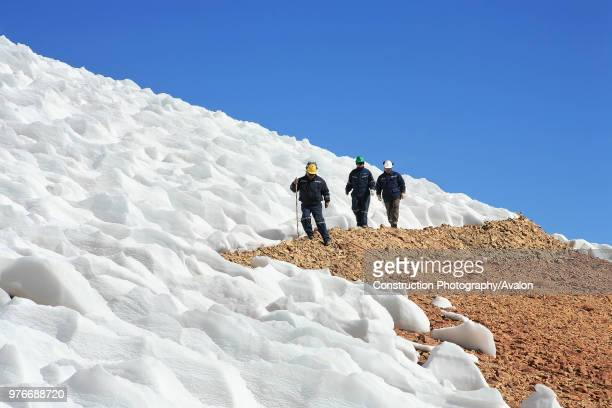 Three Miners Walking Next To Glacier In The Andes Chile