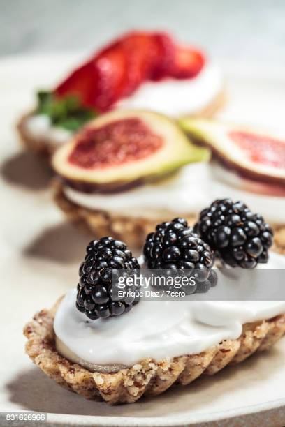 Three Mini Berry Cheesecakes on White Plate Close Up Blackberry