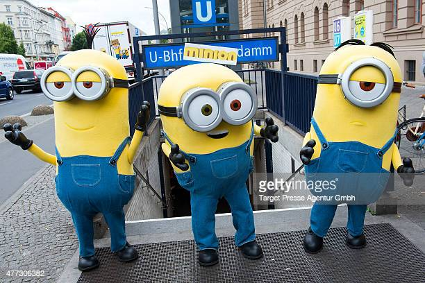 Three Minions pose at the entrance to the especially decorated underground station 'Mehringdamm' during a photocall for the film 'Minions' on June 16...