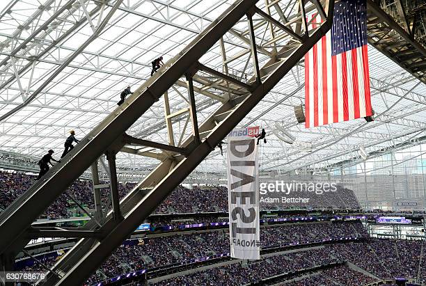 Three Minneapolis Fire Department members and one Minneapolis Police Department officer scale the rafters of US Bank Stadium where two protestors of...