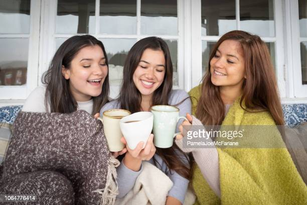 three mixed-ethnic sisters cheering with coffee mugs, cool autumn day - hygge stock pictures, royalty-free photos & images