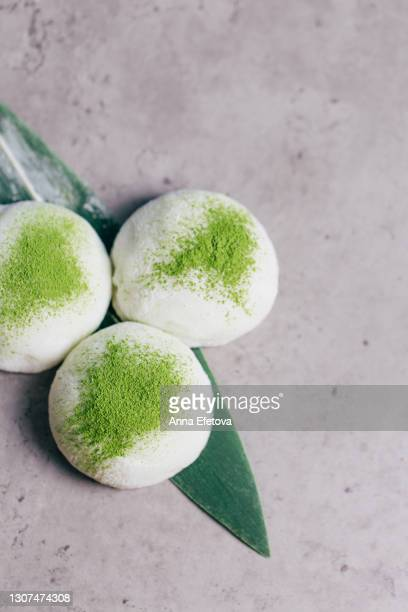 three mochi desserts with matcha tea powder on concrete textured background. traditional japanese cake. flat lay style - 大福餅 ストックフォトと画像