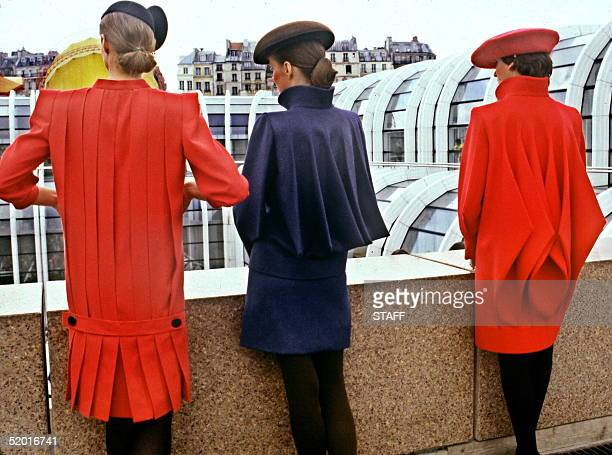 Three models display 'Pierre Cardin' s Backs' left to right a Straight dress in red woolen crepe pleated at back with a low waist half belt a blue...