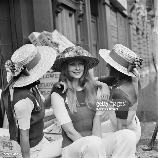 Three models in straw hats adorned with artificial fruit and flowers, UK, 7th March 1972.