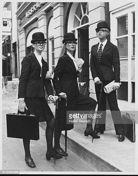 Three models sport Slimma pinstripe business suits One wears maxi culottes while another wears a midi length skirt all accessorized with bowler hats...