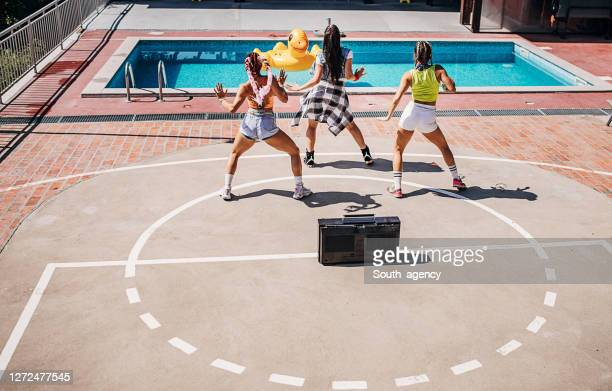 three modern female dancers dancing together outdoors by the pool - dance troupe stock pictures, royalty-free photos & images