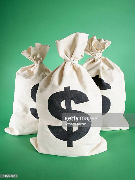 three money bags against green background - money bag stock pictures, royalty-free photos & images