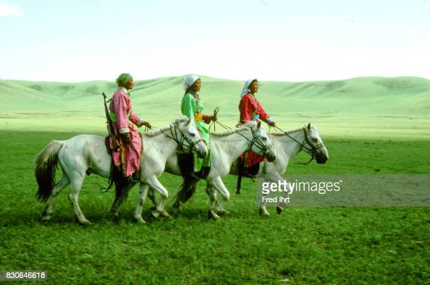 Three Mongolian Woman on horses dressed in the traditional deel Rifles over their shoulders They belong to the nomads police The deel outfit is a...