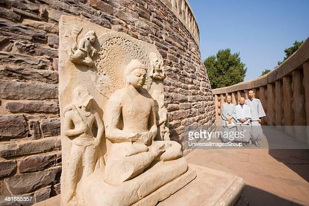 Three monks standing at a stupa Great Stupa Sanchi Bhopal Madhya Pradesh India