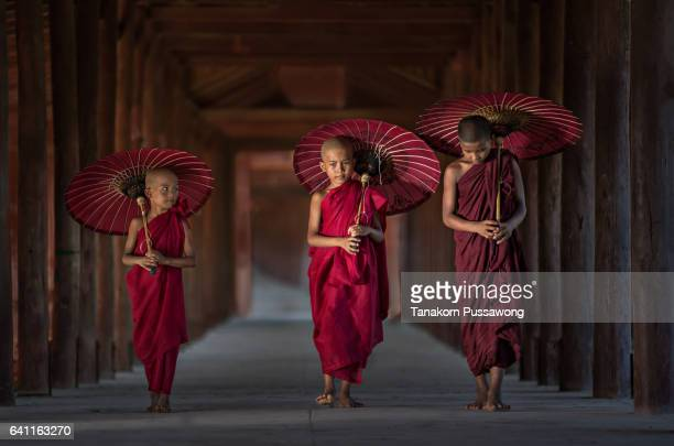 three monks walking on ancient temple - myanmar fotografías e imágenes de stock