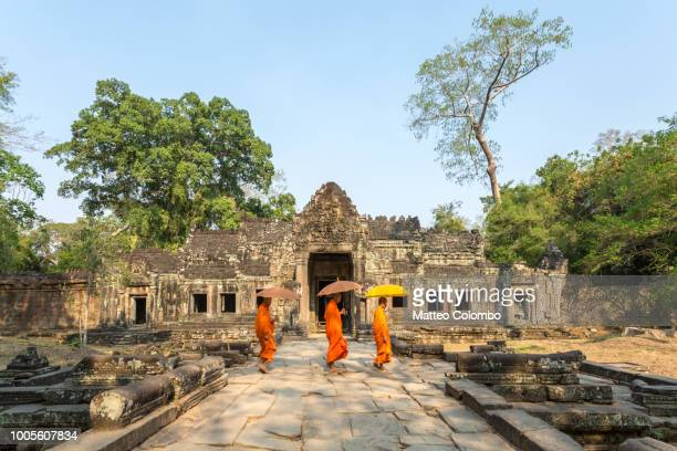 three monks with umbrellas walking inside a temple - angkor stock photos and pictures