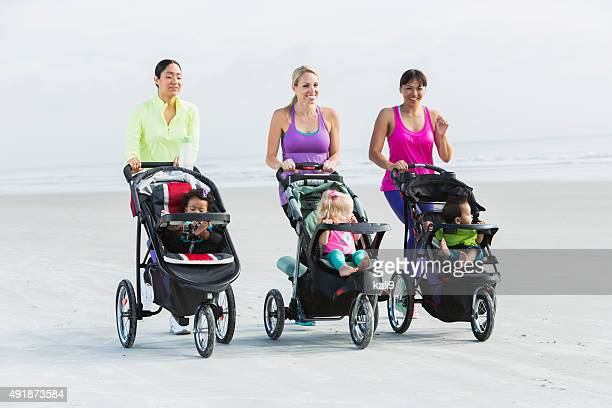 Three mothers and babies in strollers jogging on beach