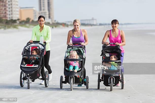 3 つの母親と赤ちゃん用ベビーカーでビーチを歩く