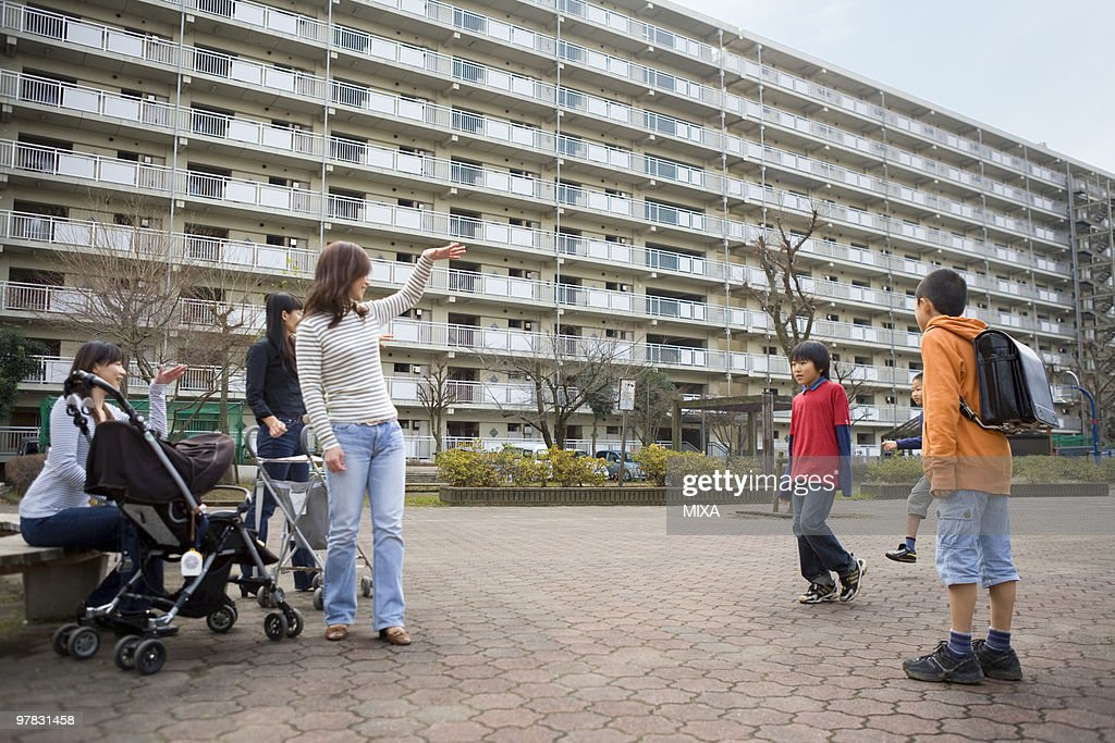Three mothers beckoning boys : Stock Photo