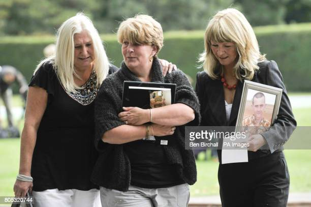Three mothers comfort each other as they hold pictures of their fallen sons, who were all killed in Afghanistan, as they came together to form a...