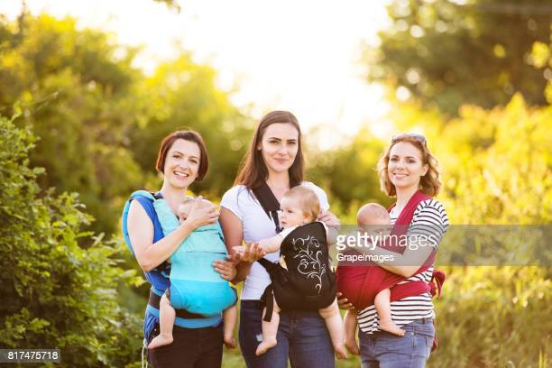 Three mothers on a walk in green nature, their children in baby carriers