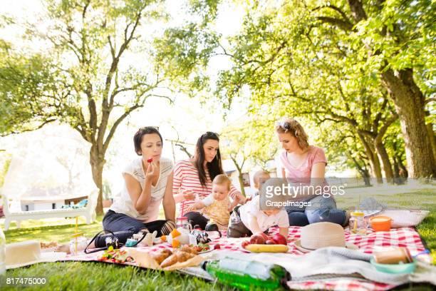 Tres madres al aire libre en la naturaleza verde con sus hijos teniendo comida campestre.