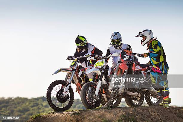three motocross riders on dirt bikes in nature. - scrambling stock photos and pictures