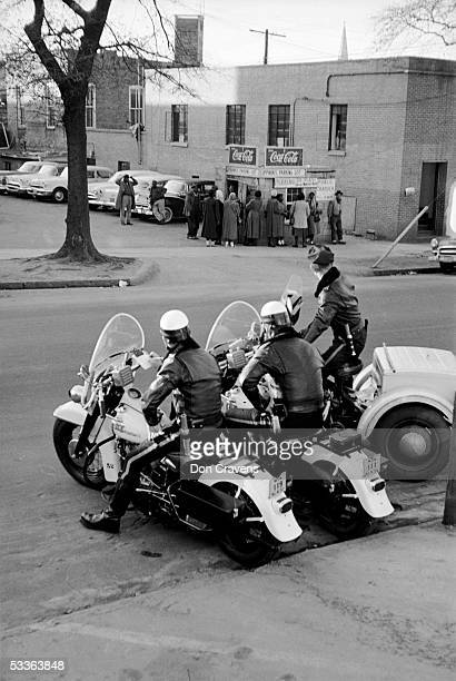 Three motorcycle police officers watch a small crowd of African Americans who wait for a car pool ride during the bus boycott Montgomery Alabama...