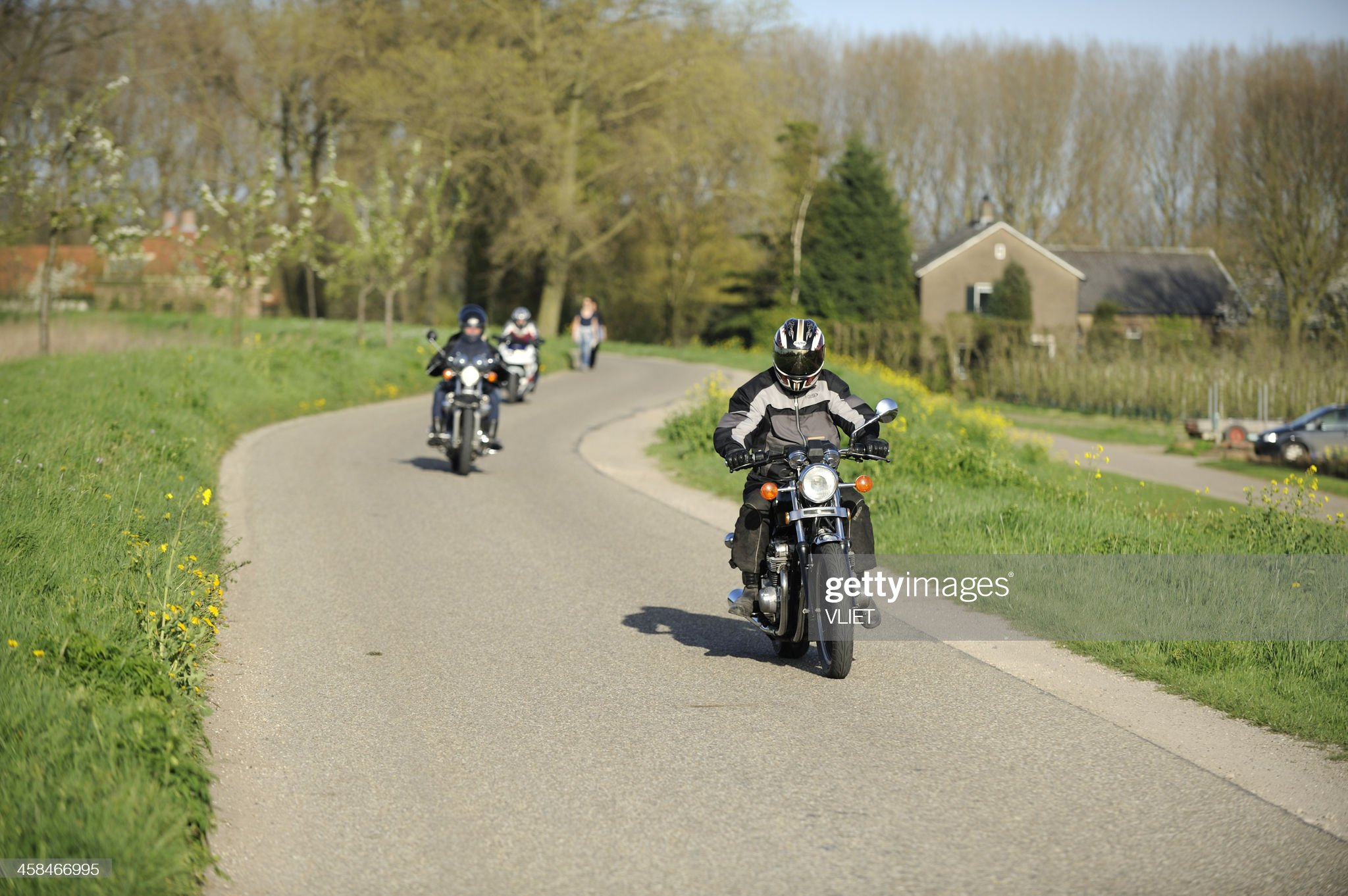 Three motorcyclists on a dyke road in the Netherlands : Bildbanksbilder