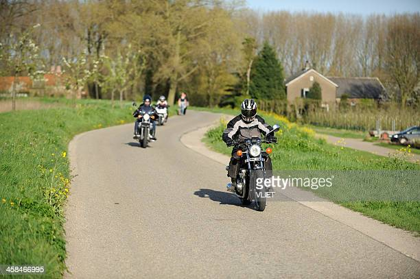 three motorcyclists on a dyke road in the netherlands - motorcycle stock pictures, royalty-free photos & images