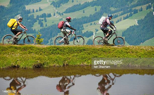Three mountain bikers reflected in pond