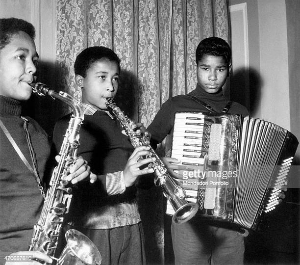 'Three mulatto guys playing as a saxophonist a clarinetist and an accordionist taking part to a band of kids at the Village of the Children a care...