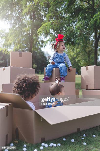 three multi ethnic babies playing outside in boxes
