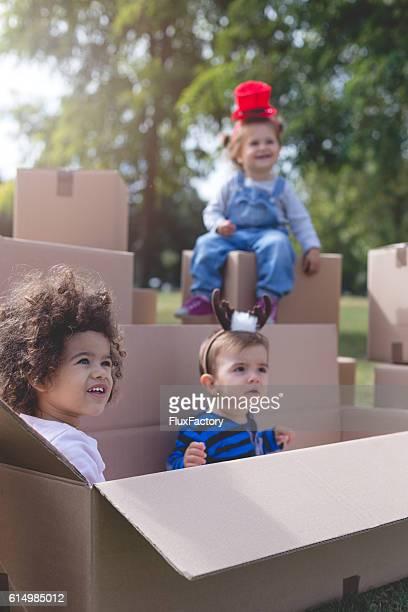 three multi ethnic babies playing outside