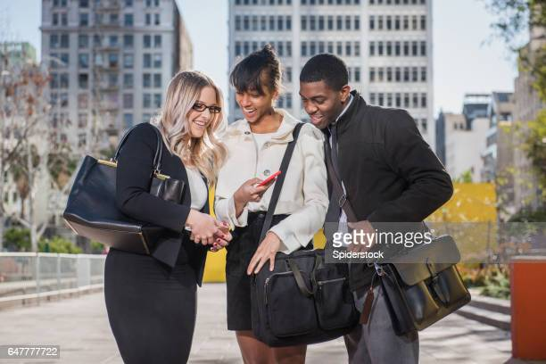 Three Multi Ethnic Millennials in business attire with mobile devices in Downtown Los Angeles