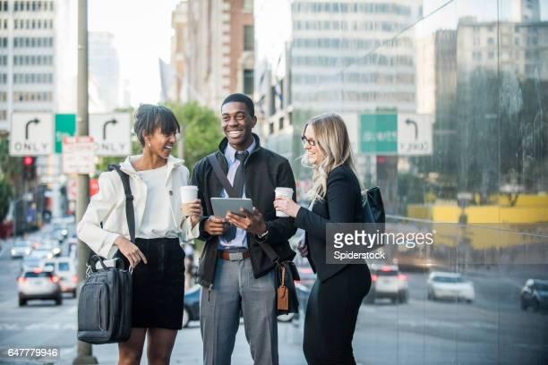 Trois Multi ethnique Millennials en tenue d'affaires avec les appareils mobiles et le café dans le centre ville de Los Angeles
