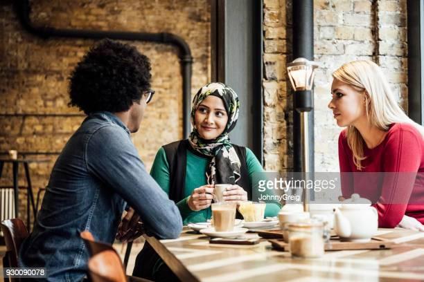Three multi racial friends enjoying coffee in cafe