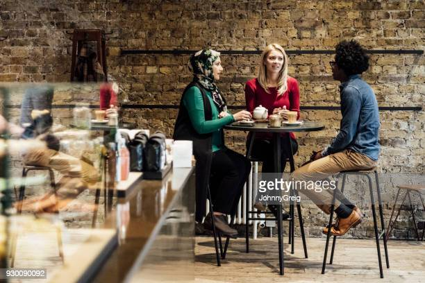 Three multi racial friends sitting on stools at table in cafe