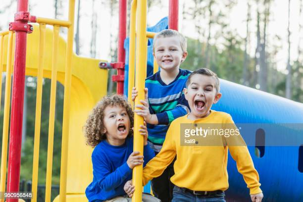 three multi-ethnic boys playing on playground - naughty america stock pictures, royalty-free photos & images