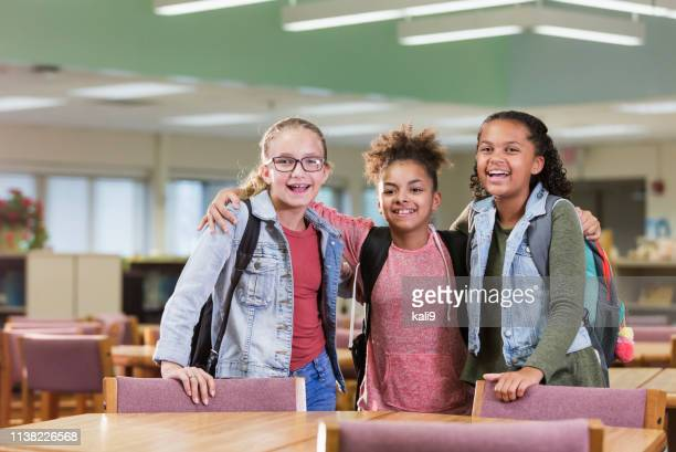 three multi-ethnic girls in elementary school library - only girls stock pictures, royalty-free photos & images