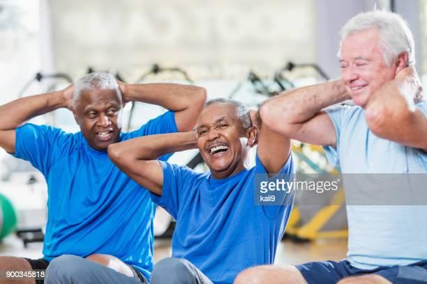 three multi-ethnic senior men in gym exercising - minority groups stock pictures, royalty-free photos & images